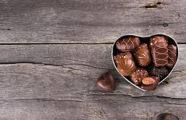 Schokoladen in einer box in form von herzen auf einem dunklen hintergrund Premium Fotos