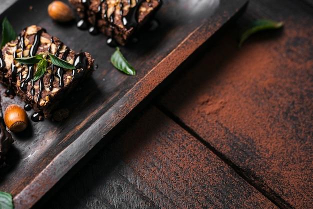 Schokoladen-nuss-schokoladenkuchen des hohen winkels auf behälter mit kakaopulver Kostenlose Fotos