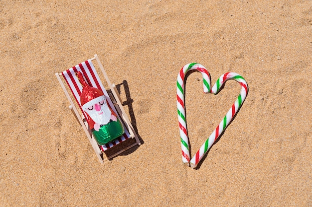 Schokoladen-sankt, die im klappstuhl auf sandigem strand stillsteht Premium Fotos