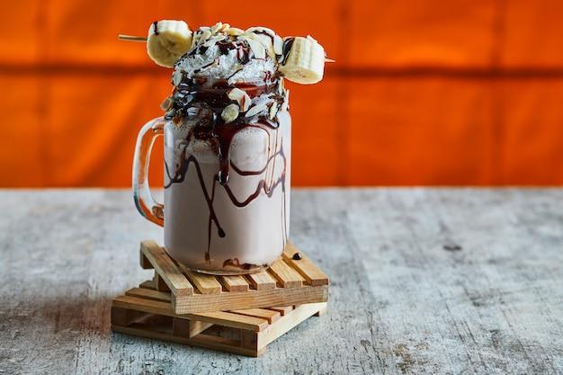 Schokoladen-smoothie mit schokoladensirup, banane und schlagsahne auf dem holzbrett in der hellen oberfläche Kostenlose Fotos