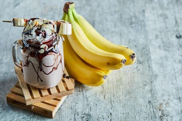 Schokoladen-smoothie mit schokoladensirup und bananenzweig Kostenlose Fotos