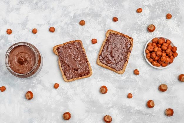 Schokoladenaufstrich oder nugatcreme mit haselnüssen im glasgefäß auf beton, copyspace Kostenlose Fotos