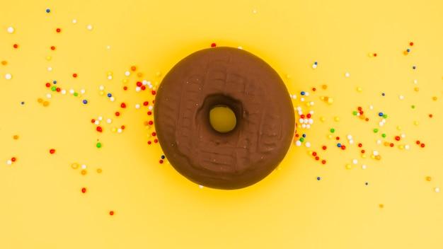 Schokoladendonut mit buntem besprüht auf gelbem hintergrund Kostenlose Fotos