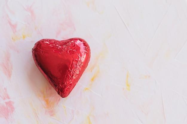 Schokoladenherz in der roten folie auf einem rosa hintergrund Premium Fotos