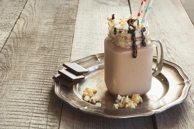 Schokoladenkaffeemilchshake mit schlagsahne diente im weckglas auf holztisch. Premium Fotos