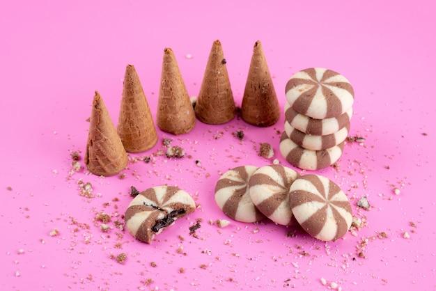 Schokoladenkekse einer vorderansicht zusammen mit hörnern auf rosa, kekskeksbonbonfarbe Kostenlose Fotos