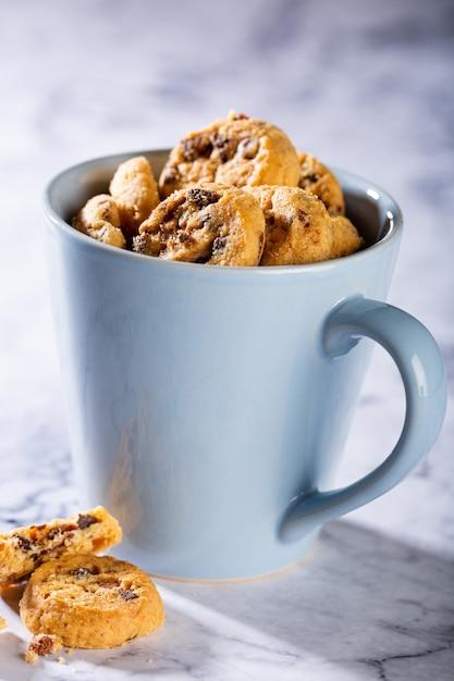 Schokoladenkekse in der blauen tasse auf marmorsteinoberfläche. selektiver fokus. speicherplatz kopieren Premium Fotos