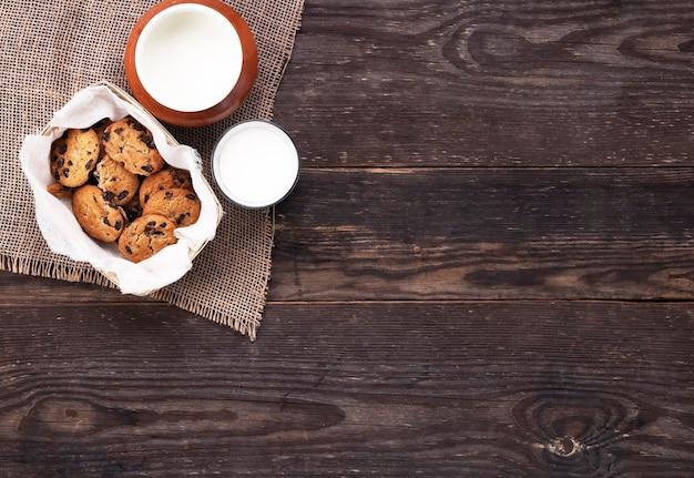 Schokoladenkekse und milch in glas und topf auf sackleinen auf einem holztisch. flach liegen. Premium Fotos