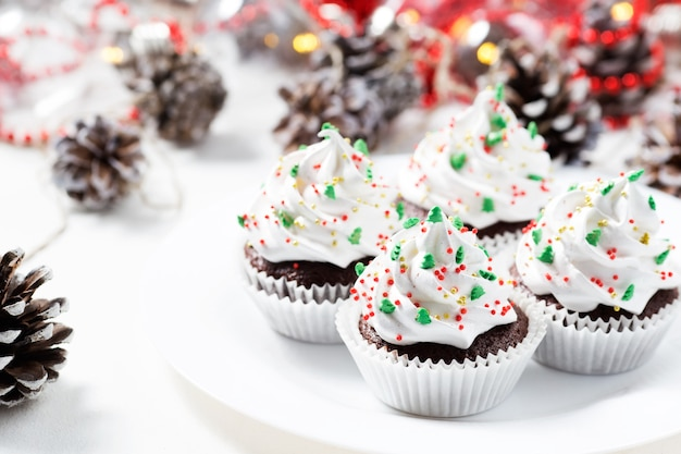Schokoladenkleine kuchen verzierten weiße sahne- und tannenbäume auf einer weißen platte. weihnachtssüßigkeiten. neujahrs-dessert Premium Fotos