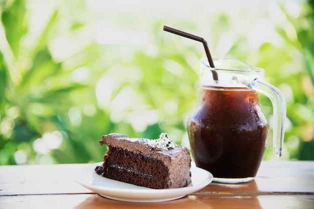 Schokoladenkuchen auf tabelle mit eiskaffee über grünem garten - entspannen sie sich mit getränk und bäckerei im naturkonzept Kostenlose Fotos