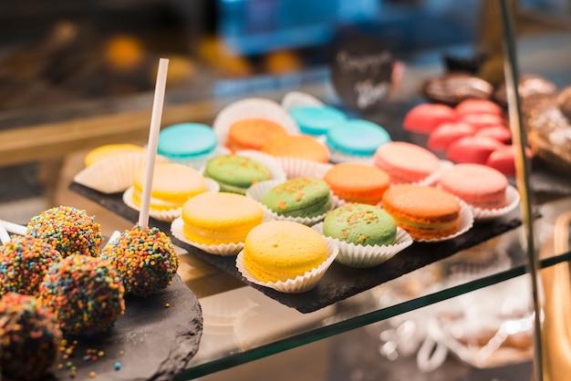Schokoladenkuchen knallt mit bunten streuseln und makronen im vitrinenschrank Kostenlose Fotos