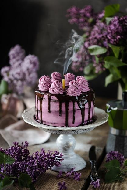 Schokoladenkuchen und ein fliederstrauß auf holztisch Premium Fotos