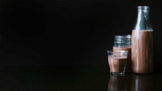 Schokoladenmilchshake im glas; glas und flasche auf schwarzem hintergrund Kostenlose Fotos