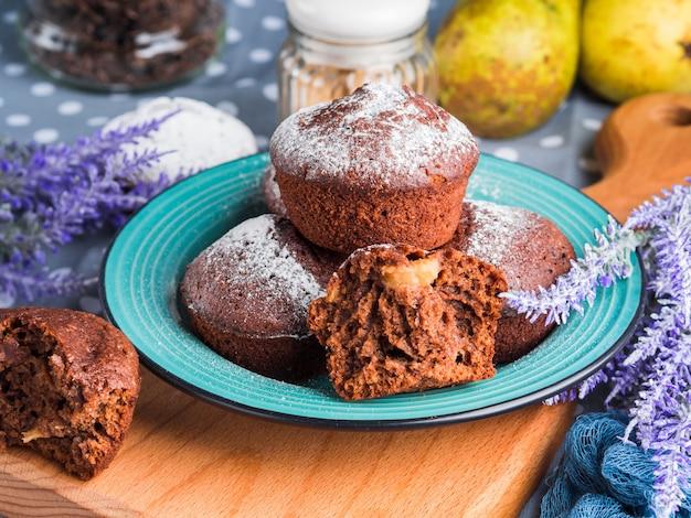 Schokoladenmuffins mit birnen und puderzucker Premium Fotos
