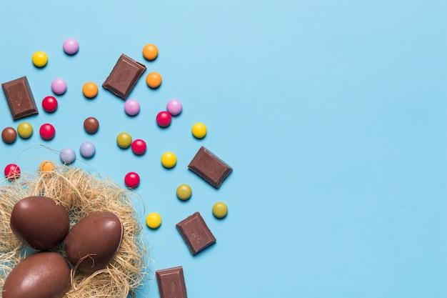 Schokoladenostereier im nest verziert mit edelsteinsüßigkeiten und schokoladenstücken auf blauem hintergrund Kostenlose Fotos
