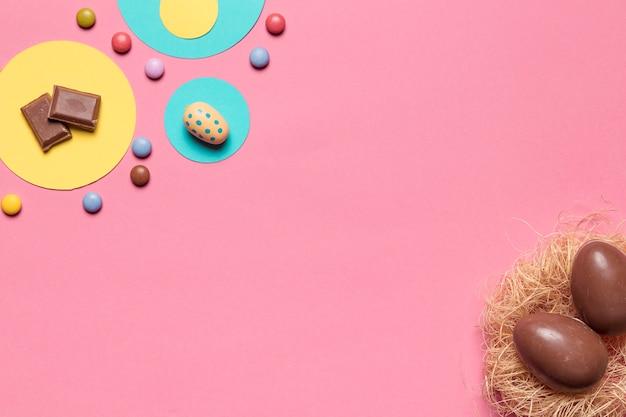 Schokoladenostereier und edelsteinsüßigkeiten mit kopienraum für das schreiben des textes auf rosa hintergrund Kostenlose Fotos