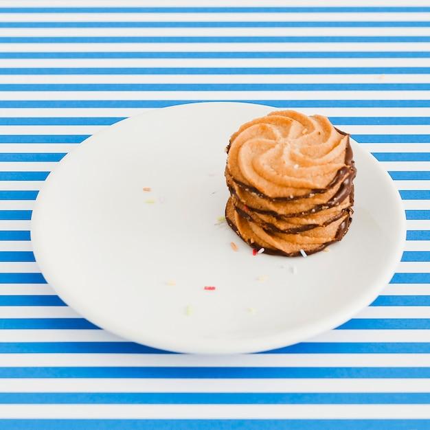 Schokoladenplätzchen auf platte über dem blauen und weißen streifenhintergrund Kostenlose Fotos