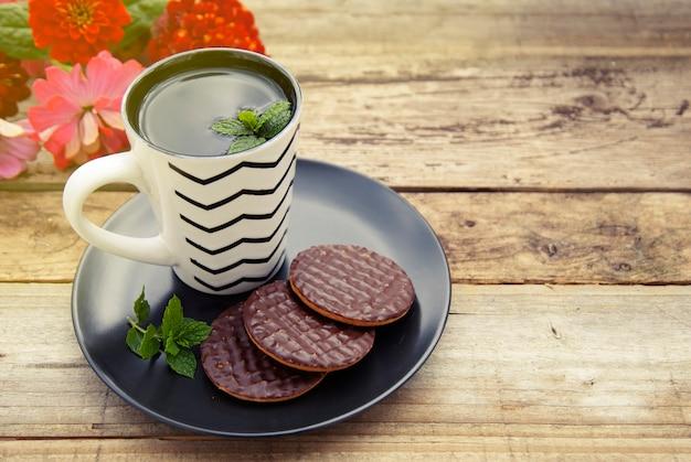 Schokoladenplätzchen mit einer tasse tee auf altem hölzernem hintergrund. Premium Fotos