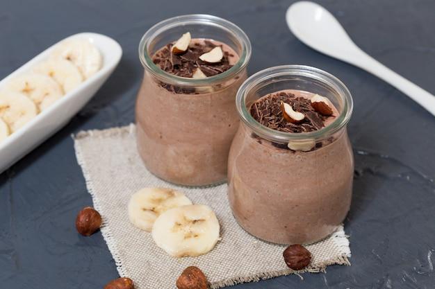 Schokoladenpudding mit chiasamen, bananen und nüssen, im glas Premium Fotos