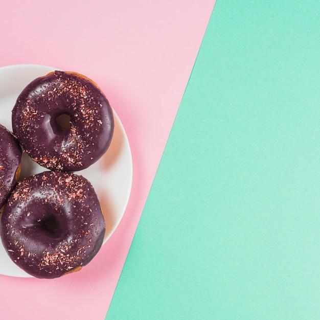 Schokoladenschaumgummiringe auf platte auf rosa und tadellosem hintergrund Kostenlose Fotos