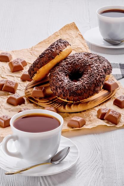 Schokoladenschaumgummiringe und -kaffee auf hellem hölzernem Premium Fotos
