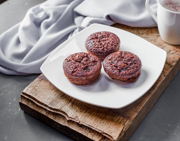 Schokoladenschokoladenkuchen in der weißen platte auf einem stück holz. Kostenlose Fotos