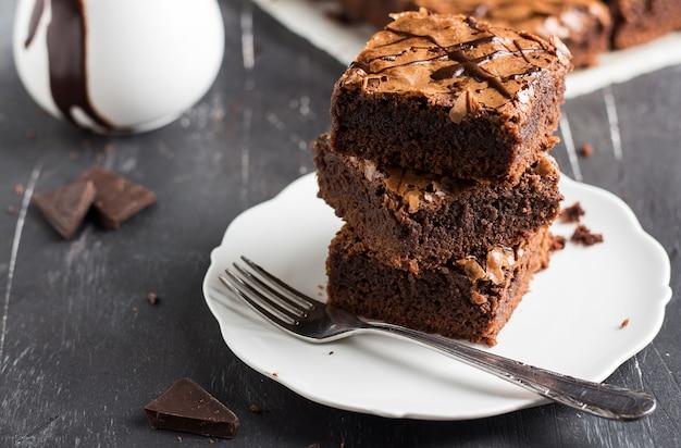 Schokoladenschokoladenkuchenkuchen-stückstapel auf selbst gemachtem gebäck der platte Kostenlose Fotos