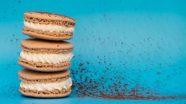 Schokoladenstaub mit makronen auf blauem hintergrund Kostenlose Fotos