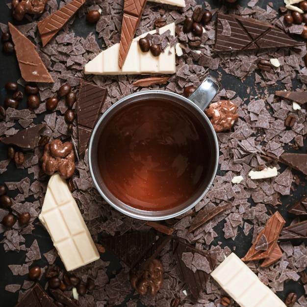 Schokoladenstücke mit gerösteten kaffeebohnen; walnüsse und geschmolzene schokolade in der tasse Kostenlose Fotos