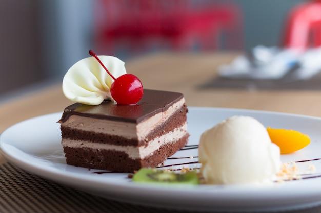 Schokoladentorte und vanilleeis mit frischen früchten und kirschen Premium Fotos
