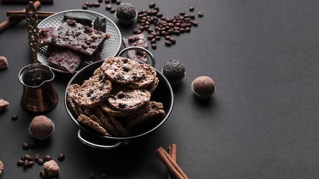 Schokoladentrüffel und gesunde haferplätzchen im gerät auf schwarzem hintergrund Kostenlose Fotos