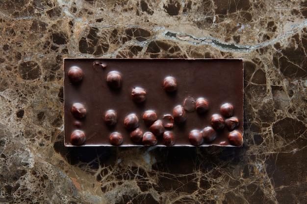 Schokoriegel mit nüssen auf einer dunklen oberfläche eines marmors. Premium Fotos