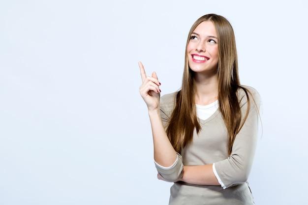 Schöne junge Frau, die oben über weißen Hintergrund zeigt. Kostenlose Fotos