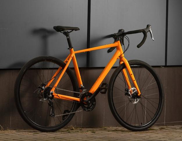 Schotterfahrrad. orange fahrrad für offrad radfahren auf grauer wand Premium Fotos