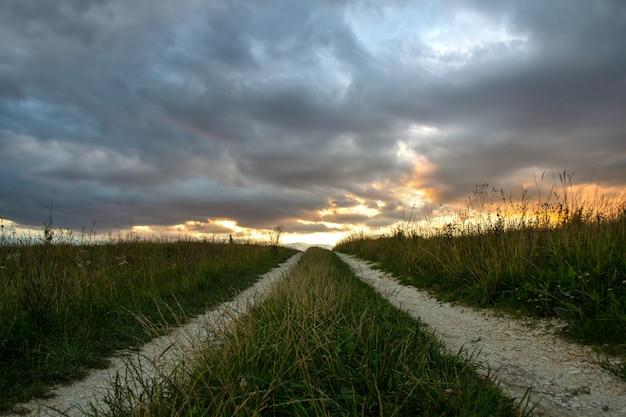 Schotterweg unter dunkelfeldern bei sonnenuntergang mit drastischem cloudscape. Premium Fotos