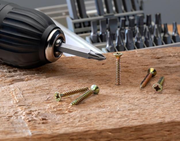 Schraube wird mit einem akku-bohrer-set in ein stück holz geschraubt. konzeptwerkzeuge und reparaturarbeiten. Premium Fotos