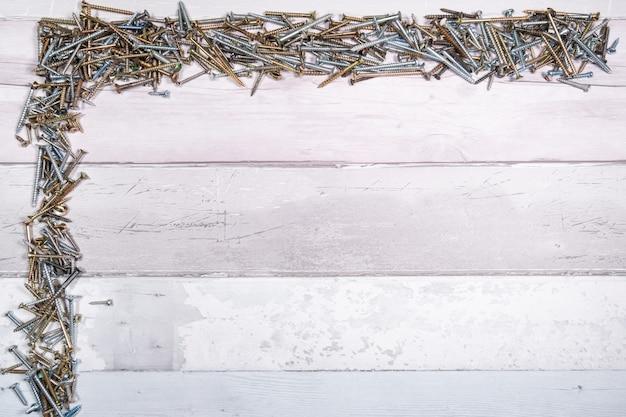 Schrauben verschiedener formen oben und an der seite eines freien raums auf einem hölzernen hintergrund. draufsicht mit platz für text Premium Fotos