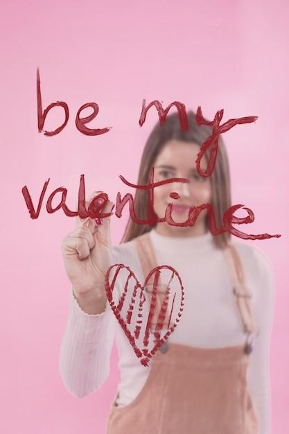 Schreiben der jungen frau seien sie mein valentinsgruß auf glas mit lippenstift Kostenlose Fotos