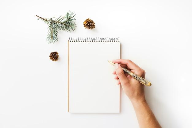 Schreiben der weiblichen hand, des papierheftes und des tannenzweigs auf weiß Premium Fotos