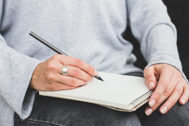 Schreiben frauenhand notizen in papier notizbuch machen. nahansicht. Premium Fotos