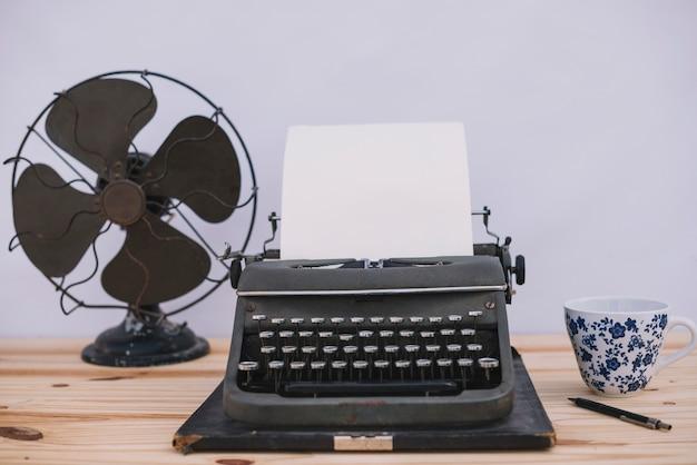 Schreibmaschine zwischen tasse und ventilator Kostenlose Fotos