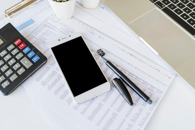 Schreibtisch des bürokaufmanns mit taschenrechner und smartphone Kostenlose Fotos