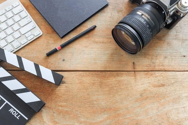 Schreibtisch des regisseurs. schindel, buch und digitalkamera auf holztisch Premium Fotos