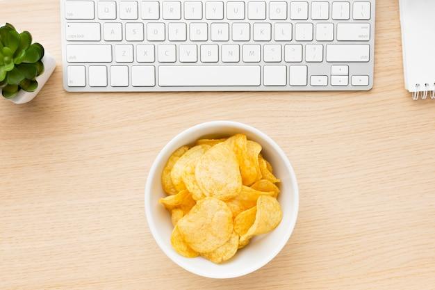 Schreibtisch mit kartoffelchips schüssel Kostenlose Fotos