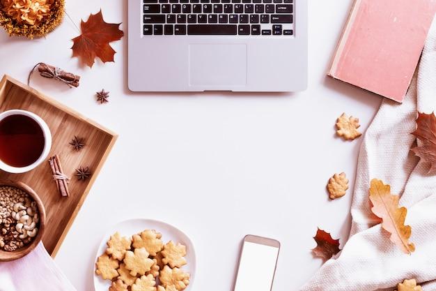 Schreibtisch mit laptop, kaffeetasse, keksen, buch und herbstlaub. draufsicht Premium Fotos