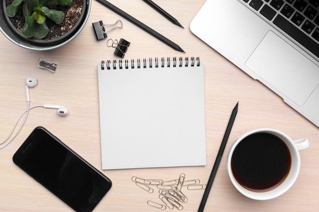 Schreibtisch mit leerem notizblock, laptop und büroartikel Premium Fotos