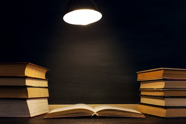 Schreibtisch vor dem hintergrund der kreidetafel, bücher im dunkeln unter dem licht einer lampe. Premium Fotos