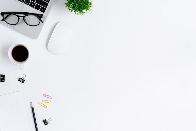 Schreibtischansicht mit laptop, maus, anlage, rosa und gelber büroklammer, kaffeetasse, notizbuch, bleistift und schwarzen gläsern Premium Fotos