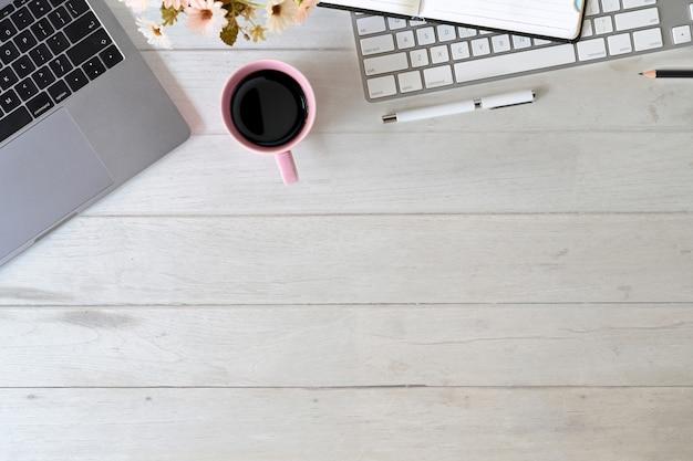 Schreibtischlaptop mit tastatur, kaffeetasse, notizbuch und büroartikel Premium Fotos