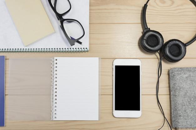 Schreibtischzubehör, notizbuch, kopfhörer, gläser auf holztisch. Premium Fotos